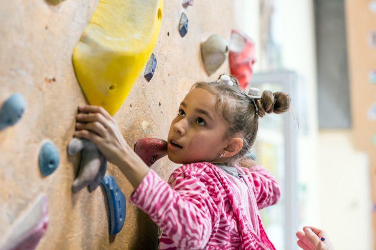 Jente som klatrer i klatrevegg
